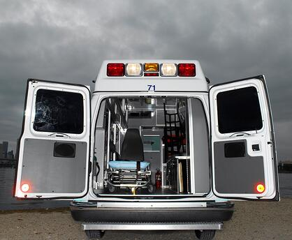 ambulance with doors open and ominous skies